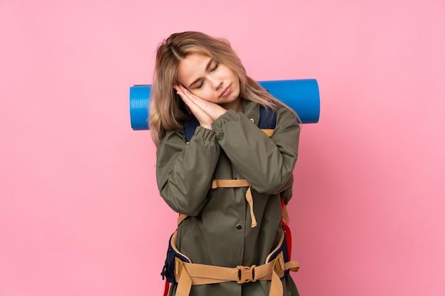 愛らしい表情で睡眠ジェスチャーを作るピンクの壁に大きなバックパックを持つティーンエイジャー登山少女