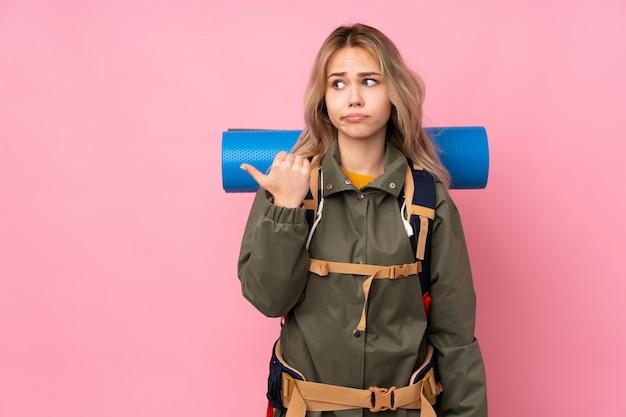 不幸で側を指しているピンクの壁に大きなバックパックを持つティーンエイジャー登山少女