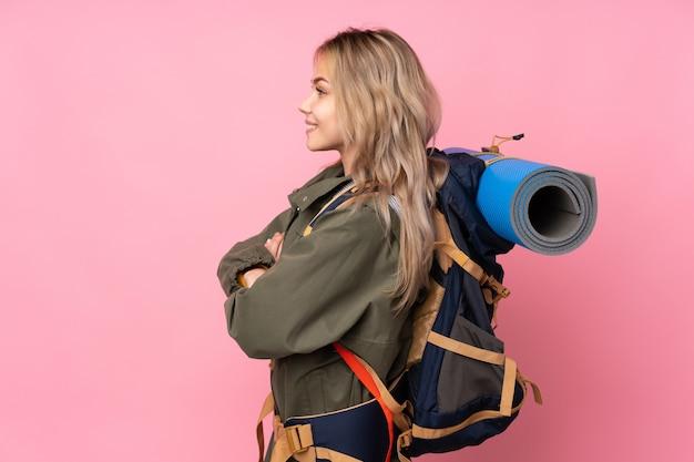 横位置でピンクの壁に大きなバックパックを持つティーンエイジャー登山少女