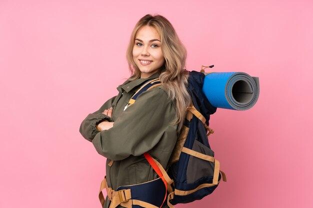 腕を組んで、楽しみにしてピンクの壁に大きなバックパックを持つティーンエイジャー登山少女