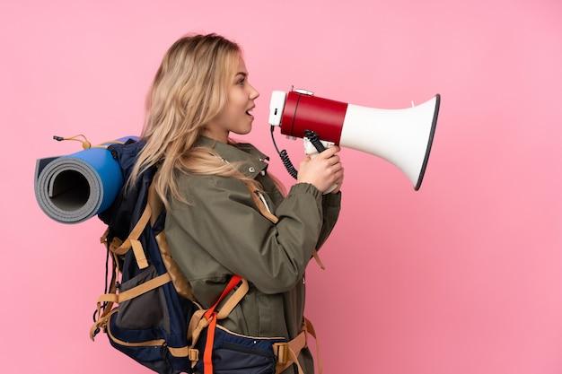 メガホンを通して叫んでピンクの壁に大きなバックパックとティーンエイジャーの登山家の女の子
