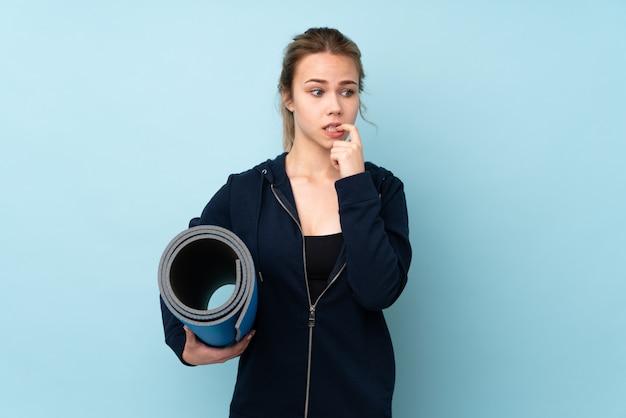 神経質で怖い青い壁にマットを保持しているティーンエイジャーの女の子