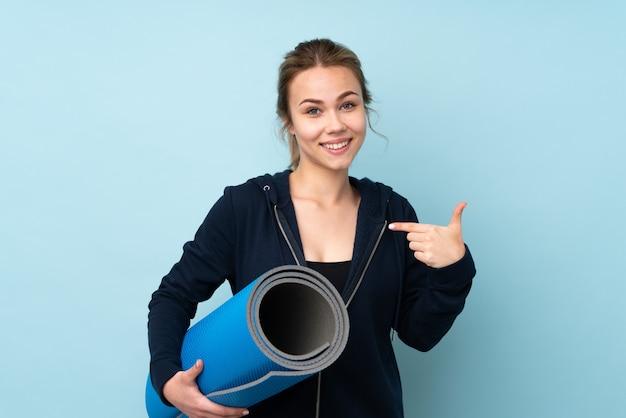 Девушка подростка держа циновку на голубой стене с выражением лица сюрприза