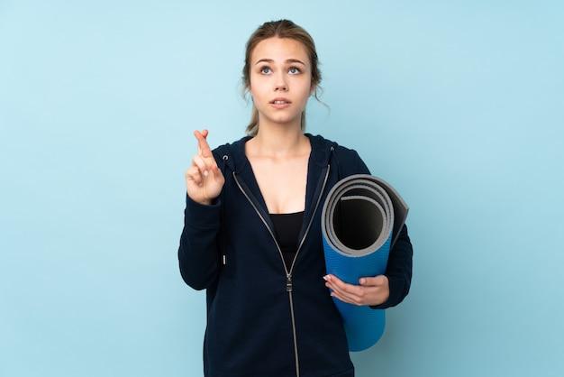 指を交差し、最高を願って青い壁にマットを保持しているティーンエイジャーの女の子