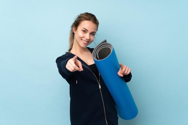 Девушка-подросток, держащая циновку на синей стене, показывает пальцем на вас, улыбаясь