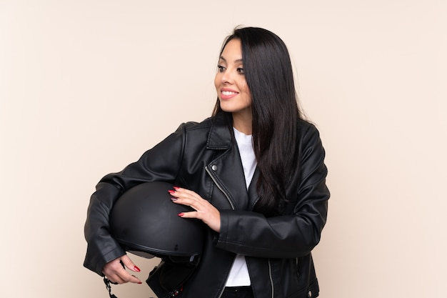 Молодая девушка держит мотоциклетный шлем над стеной смеется