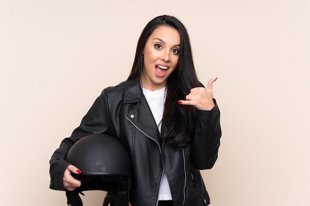 電話ジェスチャーを作る壁にオートバイのヘルメットを保持している若い女の子