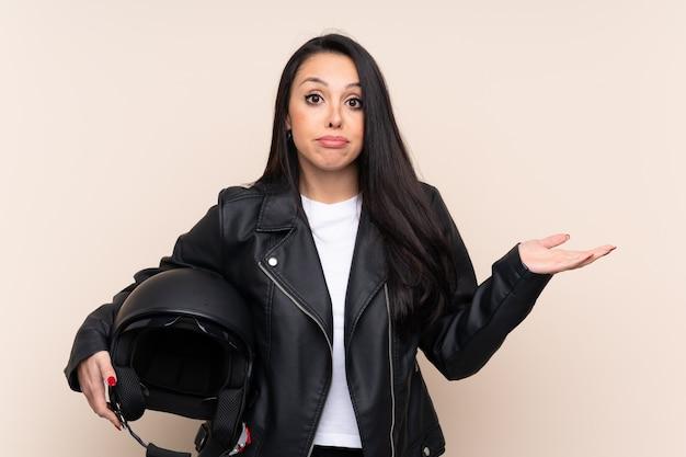 Молодая девушка держит мотоциклетный шлем над стеной с сомнением выражение лица