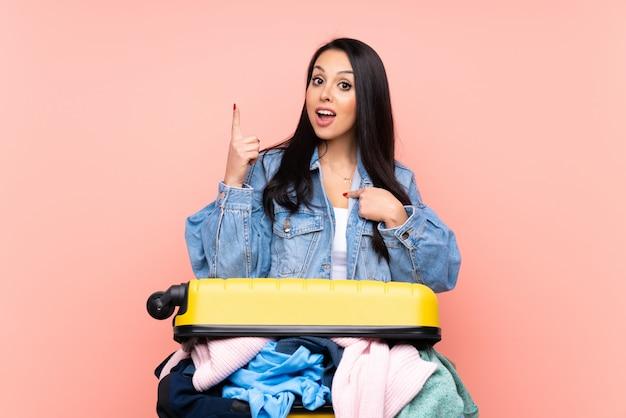 Путешественница с чемоданом одежды на розовой стене с удивленным выражением лица