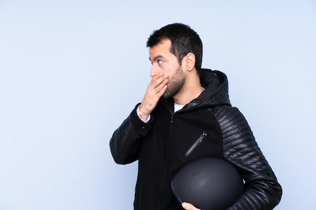 Человек с мотоциклетным шлемом, закрывающим рот руками
