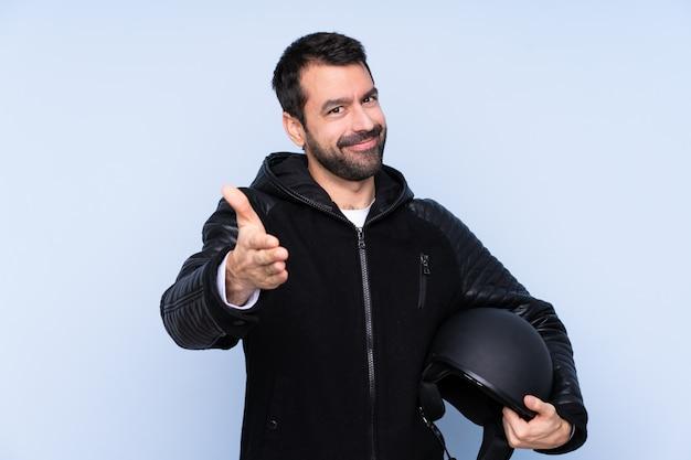 Человек с мотоциклетным шлемом пожимает руку за заключение хорошей сделки
