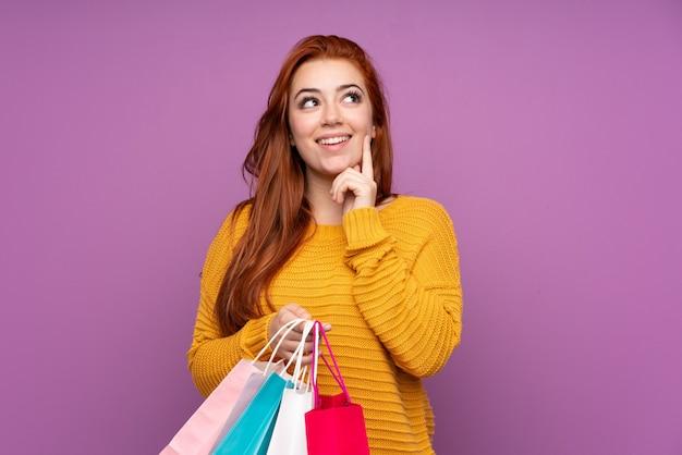 赤毛の若い女性の買い物袋を保持していると考えて