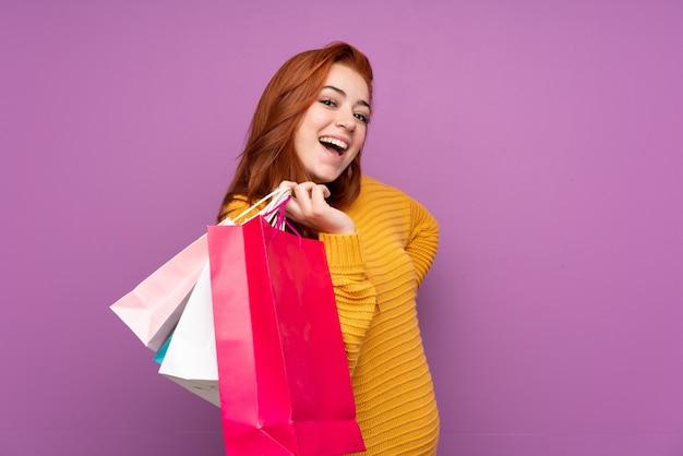 赤毛の若い女性の買い物袋を押しながら笑みを浮かべて