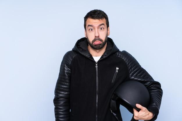 悲しいと落ち込んでいる表情でオートバイのヘルメットを持つ男