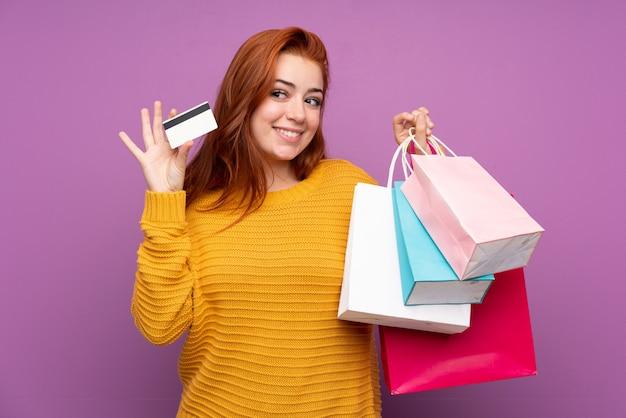 赤毛の若い女性が買い物袋とクレジットカードを保持