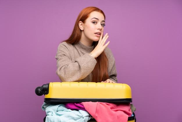 Путешественник молодая женщина с чемоданом, полным одежды шепчет что-то