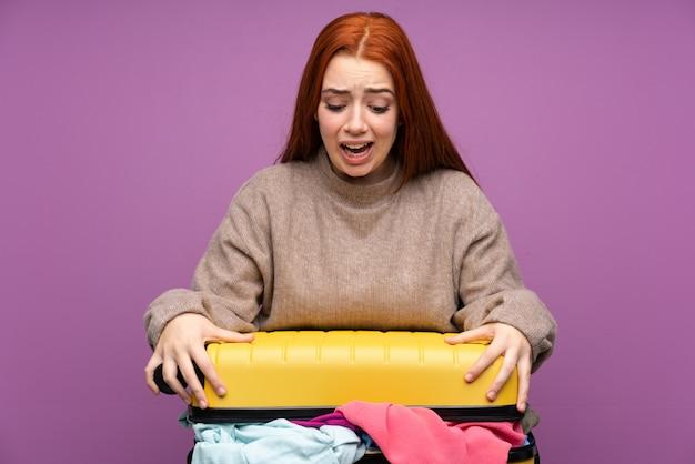 服でいっぱいのスーツケースを持つ旅行者女性