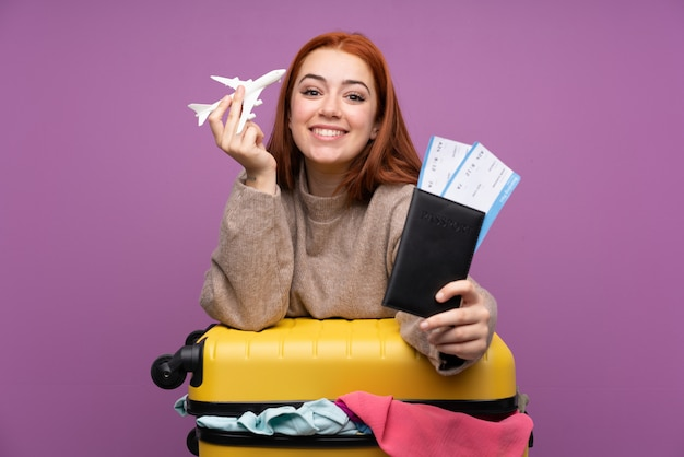 服とパスポートを保持しているスーツケースを持つ旅行者の女性