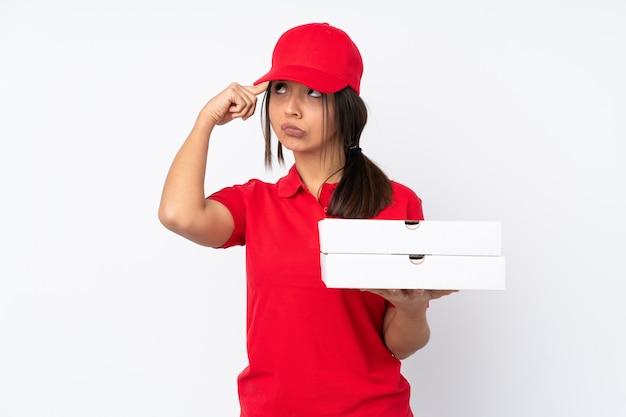 頭に指を入れて狂気のジェスチャーを作る若いピザ配達の女性