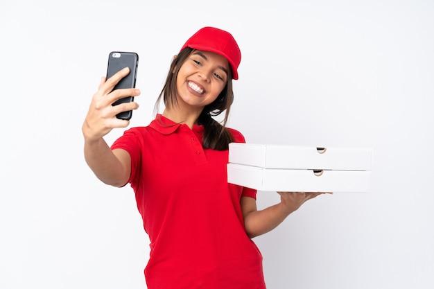 Молодая женщина доставки пиццы делает селфи