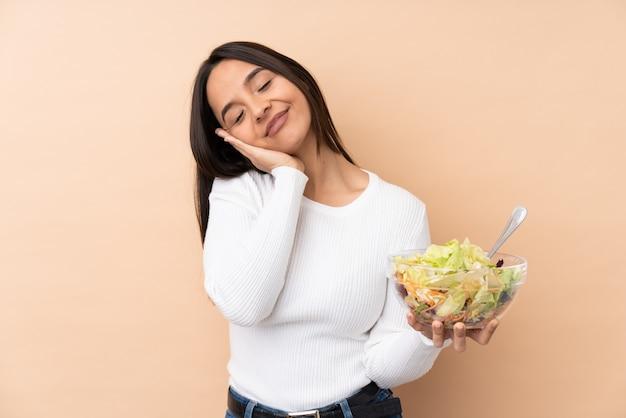 愛らしい表情で睡眠ジェスチャーを作るサラダを保持している若いブルネットの女性
