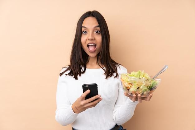 驚いてサラダを保持し、メッセージを送信する若いブルネットの女性