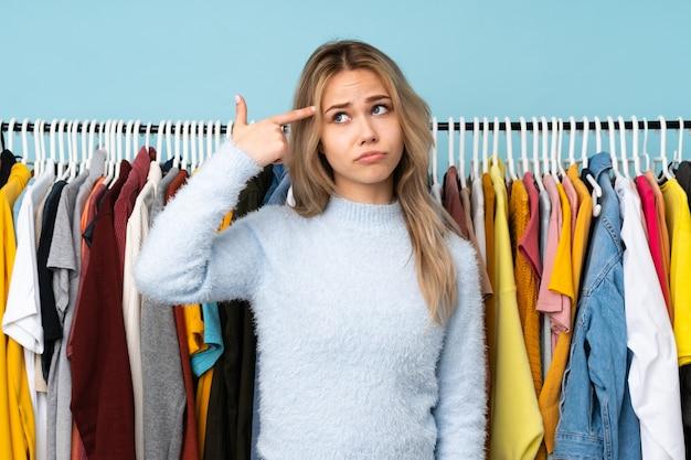 頭に指を置く狂気のジェスチャーを作る青い壁にいくつかの服を買うティーンエイジャーの女の子