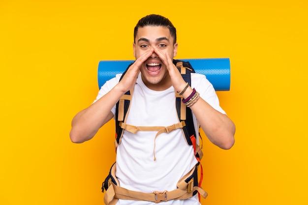 口を大きく開けて叫んで黄色の壁に大きなバックパックを持つ若い登山家のアジア人