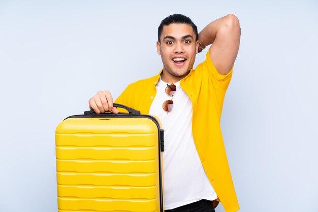 旅行スーツケースと休暇で青い壁にアジアのハンサムな男と驚いた