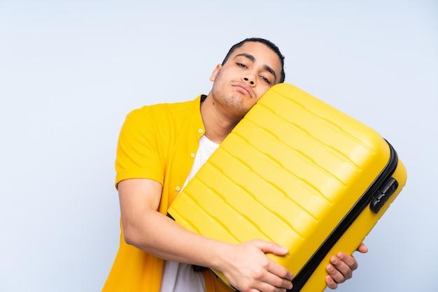 旅行スーツケースと不幸な休暇で青い壁にアジアのハンサムな男