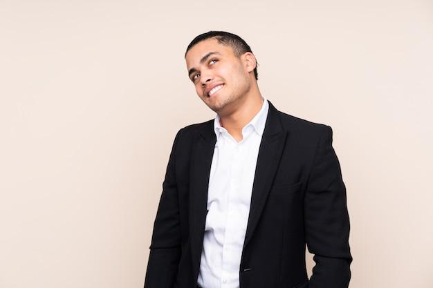 笑いと見上げるベージュの壁にアジアビジネスの男性
