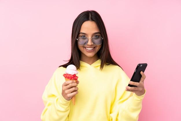 持ち帰るコーヒーと携帯電話を保持しているコルネットアイスクリームを保持している若いブルネットの女性