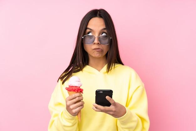 Молодая брюнетка женщина держит корнет мороженое мышления и отправки сообщения