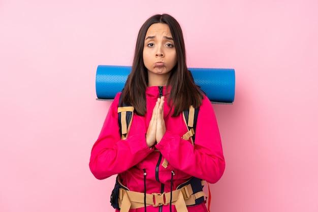 大きなバックパックを持つ若い登山家の女性は、手のひらを一緒に保ちます。人は何かを求めます