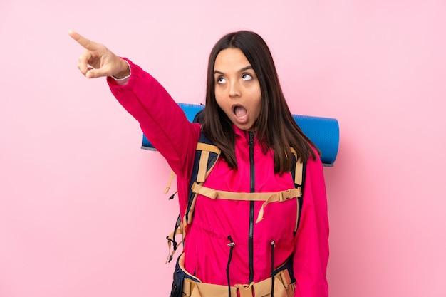 離れて指している大きなバックパックを持つ若い登山家女性