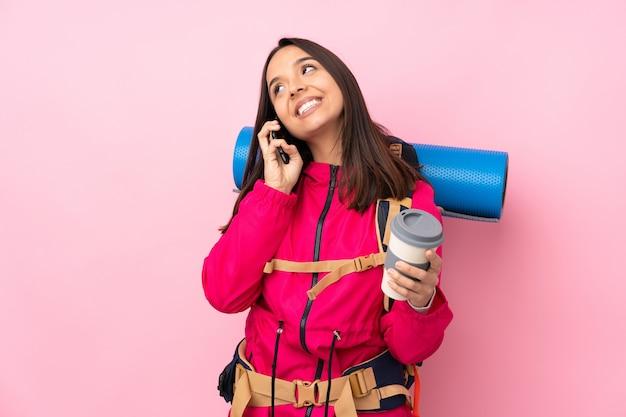 持ち帰るコーヒーと携帯電話を保持している大きなバックパックを持つ若い登山家女性
