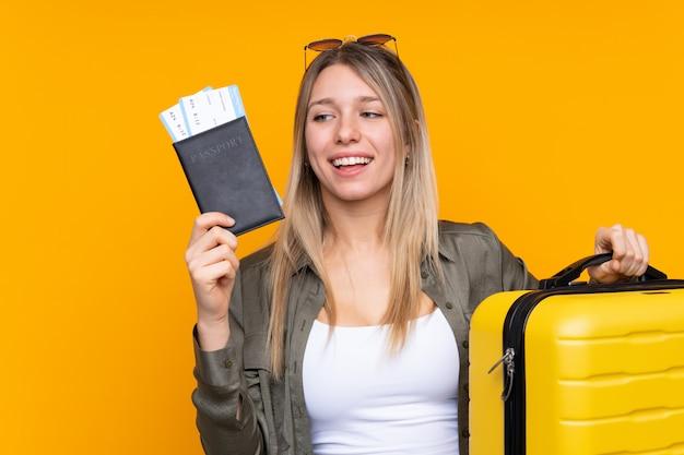 Молодая блондинка в отпуске с чемоданом и паспортом