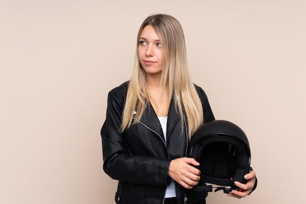 Молодая белокурая женщина с шлемом мотоцикла смотря сторону