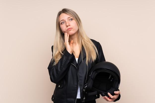 アイデアを考えてオートバイのヘルメットを持つ若いブロンドの女性