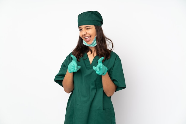 正面を指すと笑みを浮かべて白い壁に緑の制服を着た外科医女性