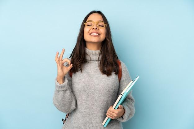 Молодая женщина смешанной расы, ходить в школу на синей стене в позе дзен