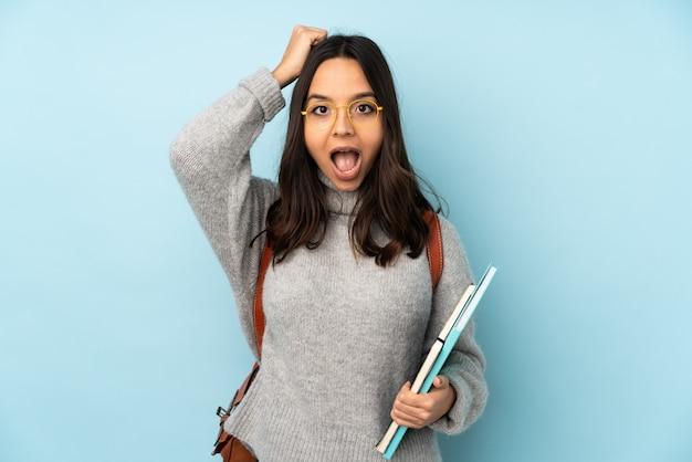 Молодая женщина смешанной расы, ходить в школу на синей стене с выражением удивления