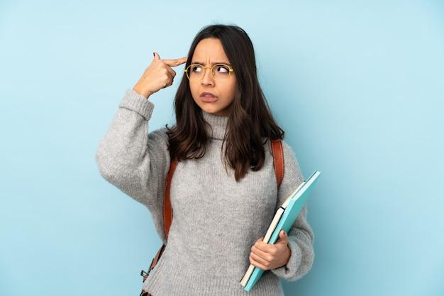 頭に指を置く狂気のジェスチャーを作る青い壁に学校に行く若い混血女性