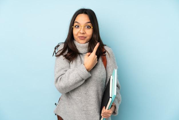 Молодая женщина смешанной расы, ходить в школу на синей стене, указывая на боковых, имеющих сомнения