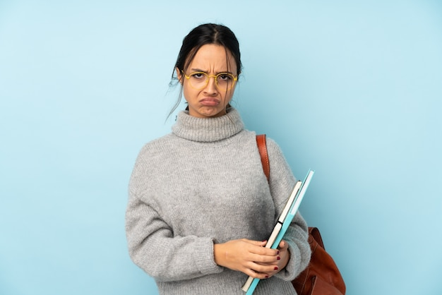 動揺を感じて青い壁に学校に行く若い混血女性