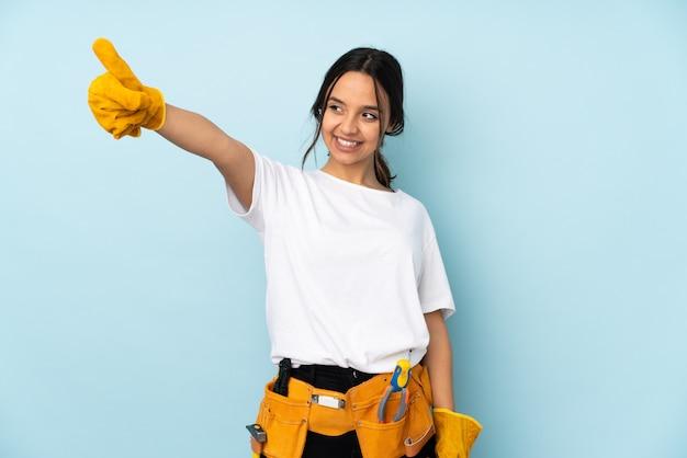 Молодая женщина электрик на голубой стене, давая пальцы вверх жест