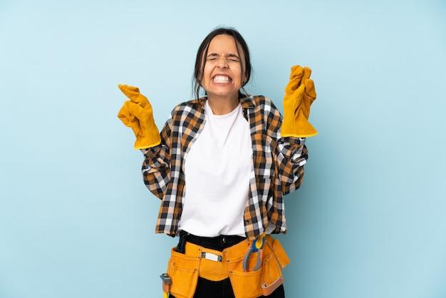Молодая женщина электрик на синей стене с пальцами, пересекая и желая лучшего