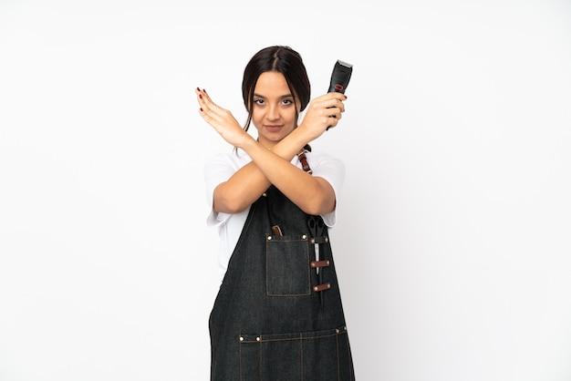 Молодая женщина-парикмахер на белой стене делает жест отрицания