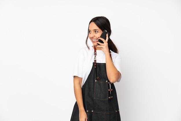 Молодая женщина-парикмахер на белой стене ведет разговор с мобильным телефоном