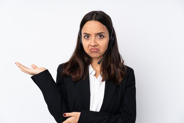 Молодая телемаркетер женщина на белой стене недовольна тем, что не понимает